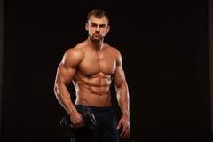 De knappe machts atletische mens met domoor kijkt vol vertrouwen vooruit De sterke bodybuilder met zes pakt, perfectioneert abs i Royalty-vrije Stock Foto