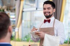 De knappe mannelijke koffiearbeider wacht een cliënt royalty-vrije stock fotografie