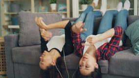 De knappe meisjes Afrikaanse Amerikaan en Aziaat genieten van favoriete muziek door oortelefoons en smartphone liggend stock video