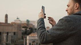 De knappe mens gebruikt smartphone Het aantrekkelijke mannetje neemt de foto op de mobiele telefoon, gebruikt de camera op cellph Stock Foto's