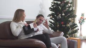 De knappe mens geeft heden aan zijn vrouw en toont creditcard Vrouw van de gift wordt opgewekt die Een kind met zijn nieuw stuk s stock videobeelden