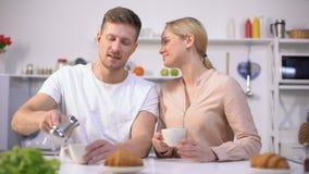 De knappe mens giet gebrouwen koffie aan leuk meisje en krijgt kus, romantische ochtend stock video