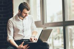 De knappe mens houdt laptop in zijn handen dichtbij het venster stock afbeelding
