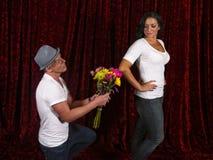 De knappe mens knielt met bloemen voor meisje royalty-vrije stock afbeelding