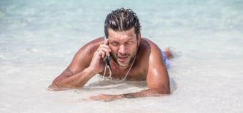 De knappe mens legt in het blauwe water van Indische Oceaan en spreekt telefonisch Stock Foto's