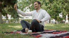 De knappe mens maakt selfie foto in het park, zittend op het gras stock footage