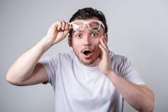 De knappe mens met varkenshaar en glazen is verrast om zijn mond op een witte achtergrond te openen royalty-vrije stock afbeelding