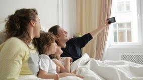 De knappe Mens neemt een Foto door Zijn Smartphone Positieve Familie Selfie met Moeder, Vader en Twee Kinderen die liggen stock videobeelden
