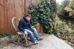 De knappe mens ontspant in uitstekende schommelstoel met telefoon in tuin Royalty-vrije Stock Afbeeldingen