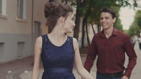 De knappe mens probeert de achterstand inloopt mooi meisje Jonge man en vrouw die pret hebben stock footage