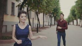 De knappe mens probeert de achterstand inloopt mooi meisje Man en Vrouw die Pret hebben stock video