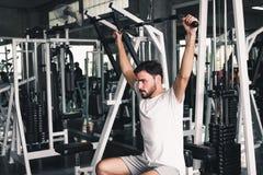 De knappe mens roeit oefening met bodybuildermateriaal in geschiktheidsclub , Portret van de sterke mens die uitwerkend calorieën stock afbeelding