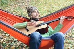 De knappe mens in warme hoed en de sjaal spelen op gitaar terwijl het zitten in een hangmat in de herfst bos het Kamperen levenss Stock Foto