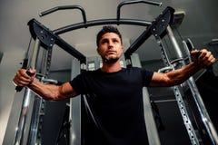 De knappe mens werkt in gymnastiek op trainer uit Stock Afbeeldingen