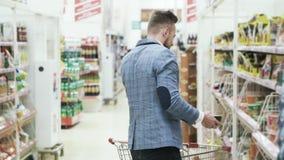 De knappe mens in wit overhemd spreekt op telefoon en het kopen kruidenierswinkels in supermarkt stock video