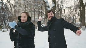 De knappe mensen werpen de sneeuwballen in het de winterpark stock video