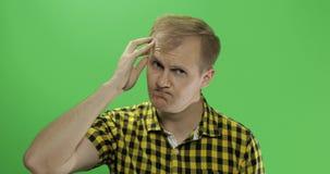 De knappe nadenkende mens die in geel overhemd in de camera kijken en denkt stock afbeeldingen