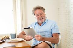 De knappe oudste trok de oude mens terug thuis gebruikend tablet met vreugde terwijl het hebben van ontbijt royalty-vrije stock foto