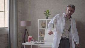 De knappe positieve, succesvolle en tevreden mens in witte robe die met röntgenstraal dansen dient binnen moderne kliniek in De a stock video