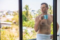 De knappe shirtless spier jonge mens het drinken koffie in de vroege ochtend op het balkon en geniet van de mening royalty-vrije stock afbeeldingen