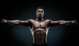 De knappe spier en bodybuilder die bewapent outstretch stellen houden royalty-vrije stock afbeelding