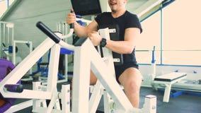 De knappe sportieve mens oefent en glimlacht in geschiktheidsclub en gymnastiekcentrum uit stock video