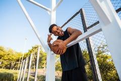 De knappe Sterke mens houdt bal op het basketbalhof Mens met een bal, sportuitrusting, sportcompetities Stock Foto's