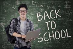 De knappe student houdt laptop in klasse stock foto