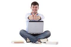 De knappe student met computer toont duimen Stock Foto