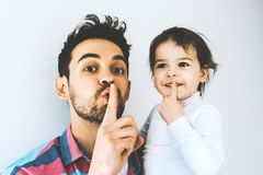 De knappe vader en de mooie dochter maken stil gebaar fatherhood De papa toont stil gebaar samen met zijn meisje royalty-vrije stock afbeelding