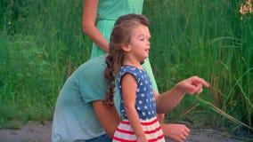 De knappe vader richt op iets, luistert zijn dochter aan hem, familieconcept, die in park op zonsondergang lopen stock footage