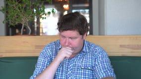 De knappe vette mens in overhemd hoest in koffie stock video
