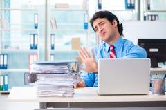 De knappe zakenman ongelukkig met het bovenmatige werk in het bureau royalty-vrije stock afbeelding