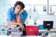 De knappe zakenman ongelukkig met het bovenmatige werk in het bureau stock afbeelding