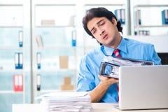 De knappe zakenman ongelukkig met het bovenmatige werk in het bureau royalty-vrije stock foto's
