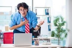 De knappe zakenman ongelukkig met het bovenmatige werk in het bureau stock afbeeldingen