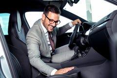 De knappe zakenman zit in een nieuwe auto in het autohandel drijven royalty-vrije stock afbeeldingen