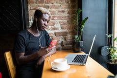 De knappe zitting van de afro Amerikaanse mens bij koffie, het luisteren muziek en het bekijken het telefoonscherm stock fotografie