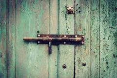 De knopachtergrond en textuur van de Grunge groene houten deur stock foto