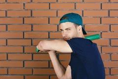 De knuppel van het honkbal De kerel in donkerblauwe t-shirt houdt heldergroene knuppel stock afbeelding