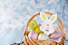 De koekjes, de konijntjes en de eieren van Pasen in een mand op lichtblauwe achtergrond Stock Afbeeldingen