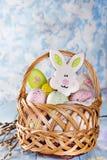 De koekjes, de konijntjes en de eieren van Pasen in een mand op lichtblauwe achtergrond Stock Foto