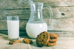 De koekjes, de kruik en het glas van de havermeelchocoladeschilfer melk, rustieke houten achtergrond Stock Afbeeldingen