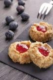 De koekjes maakten van hazelnoot shortcake met aardbeijam binnen op een zwart servet met bosbessen royalty-vrije stock fotografie