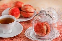 De koekjes met aardbeiroom wordt behandeld met bestrooit o, Rode ronde koekjes op een dienblad, kop thee op een houten achtergron Royalty-vrije Stock Fotografie
