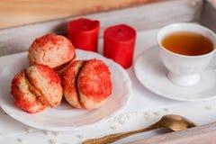 De koekjes met aardbeiroom wordt behandeld met bestrooit o, Rode ronde koekjes op een dienblad, kop thee op een houten achtergron Stock Afbeeldingen