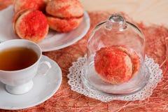 De koekjes met aardbeiroom wordt behandeld met bestrooit o, Rode ronde koekjes op een dienblad, kop thee op een houten achtergron Stock Afbeelding