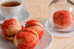 De koekjes met aardbeiroom wordt behandeld met bestrooit o, Rode ronde koekjes op een dienblad, kop thee op een houten achtergron Stock Foto