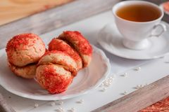 De koekjes met aardbeiroom wordt behandeld met bestrooit o, Rode ronde koekjes op een dienblad, kop thee op een houten achtergron Royalty-vrije Stock Foto