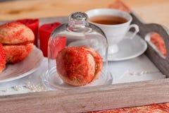 De koekjes met aardbeiroom wordt behandeld met bestrooit o, Rode ronde koekjes op een dienblad, kop thee op een houten achtergron Royalty-vrije Stock Foto's